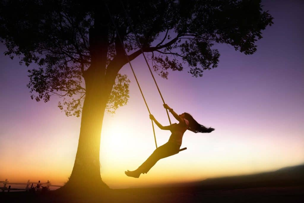 Relaxed happy woman on swing swinging with gay abandon