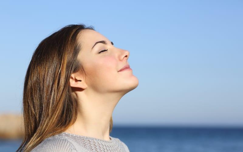 Happy woman breathing in fresh air on a beach