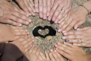 women's hands in a circle around a heart