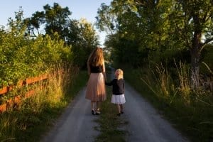 Highly sensitive mother and daughter walking down a lane