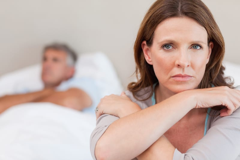 Woman suffering menopausal depression and anger with husband who's asleep in bed