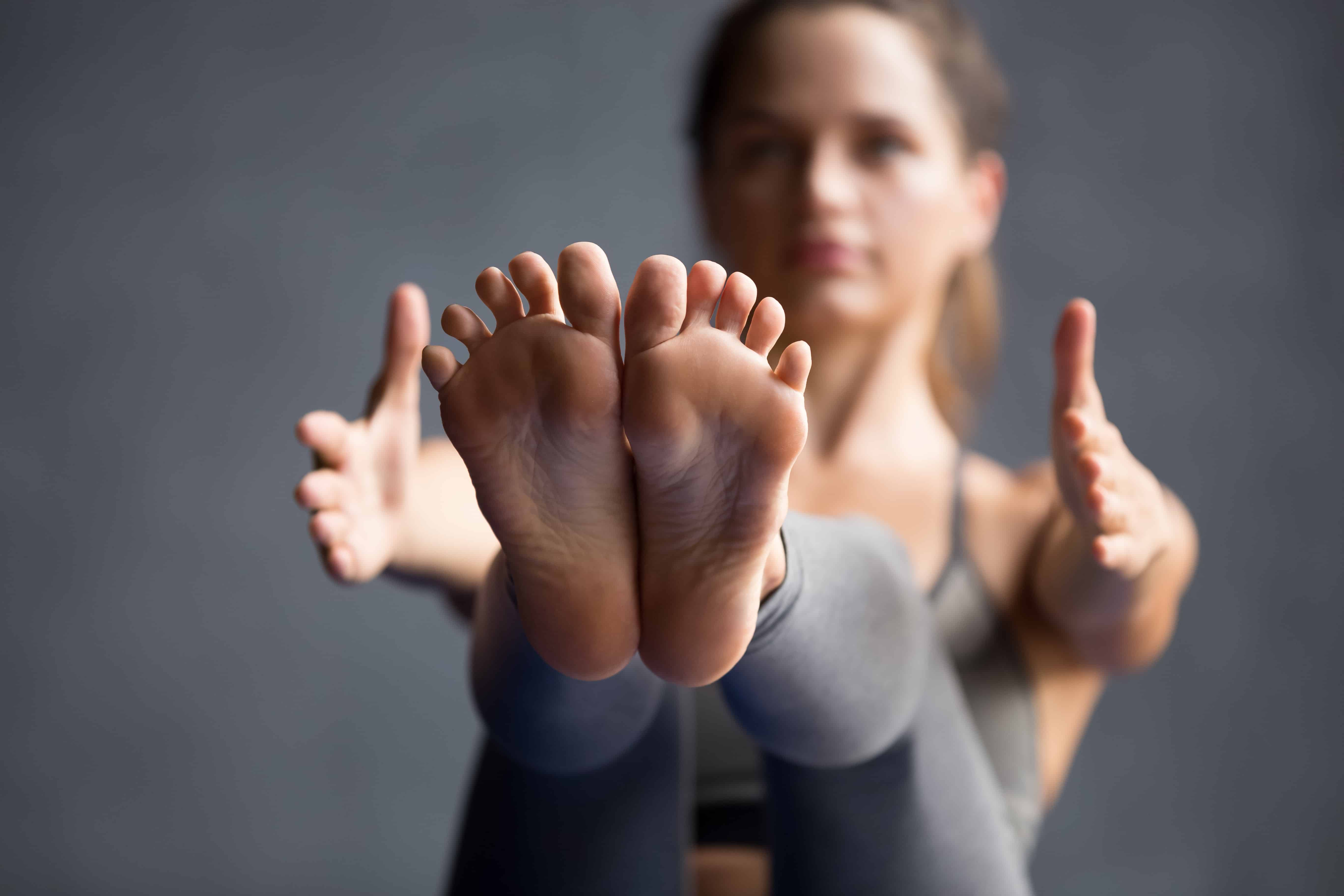 Young sporty woman practicing yoga, doing Paripurna Navasana exercise, boat pose, working out wearing sportswear grey pants, working out, indoor close up view of legs, yoga studio, focus on feet