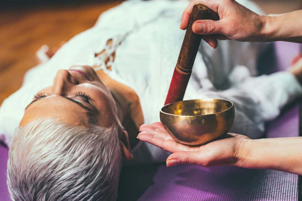 Woman lying deeply relaxed in a sound bath