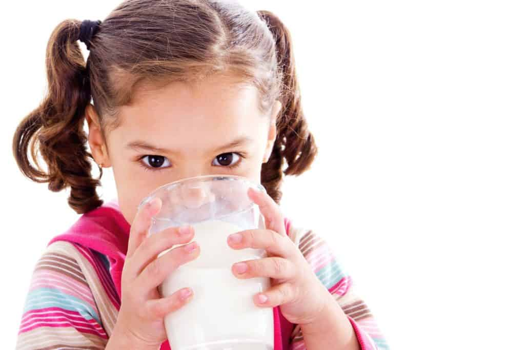 Girl drinking a glass of milk to show it could be causing her eczema