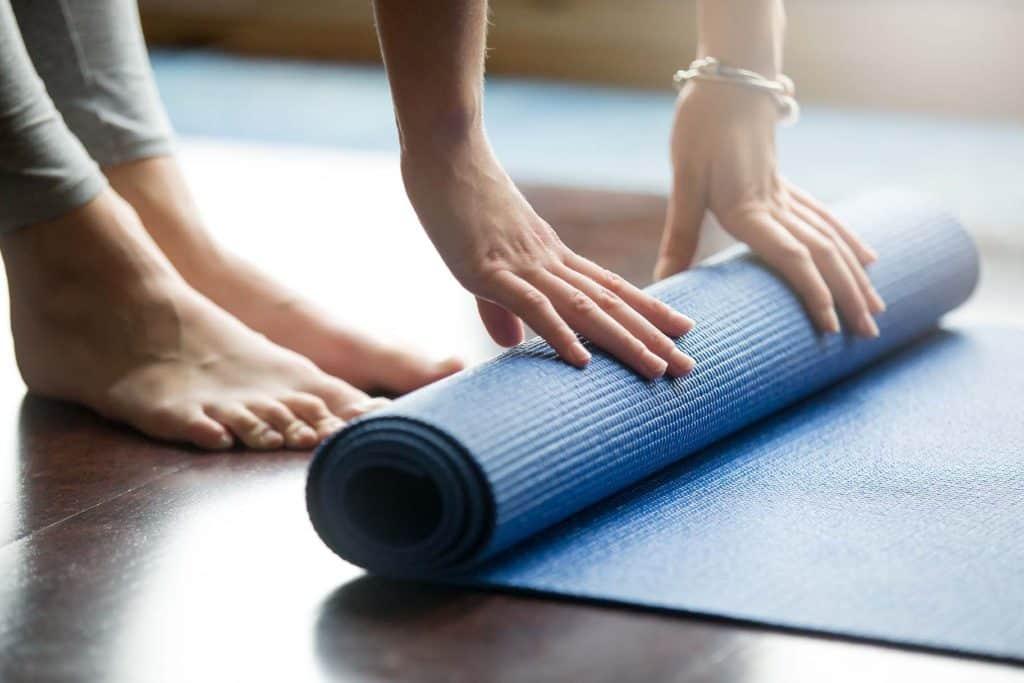 Woman rolling a yoga mat for ashtanga yoga