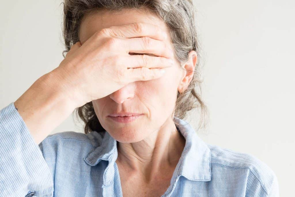 Woman holding her forehead in pain due to an emotional upset