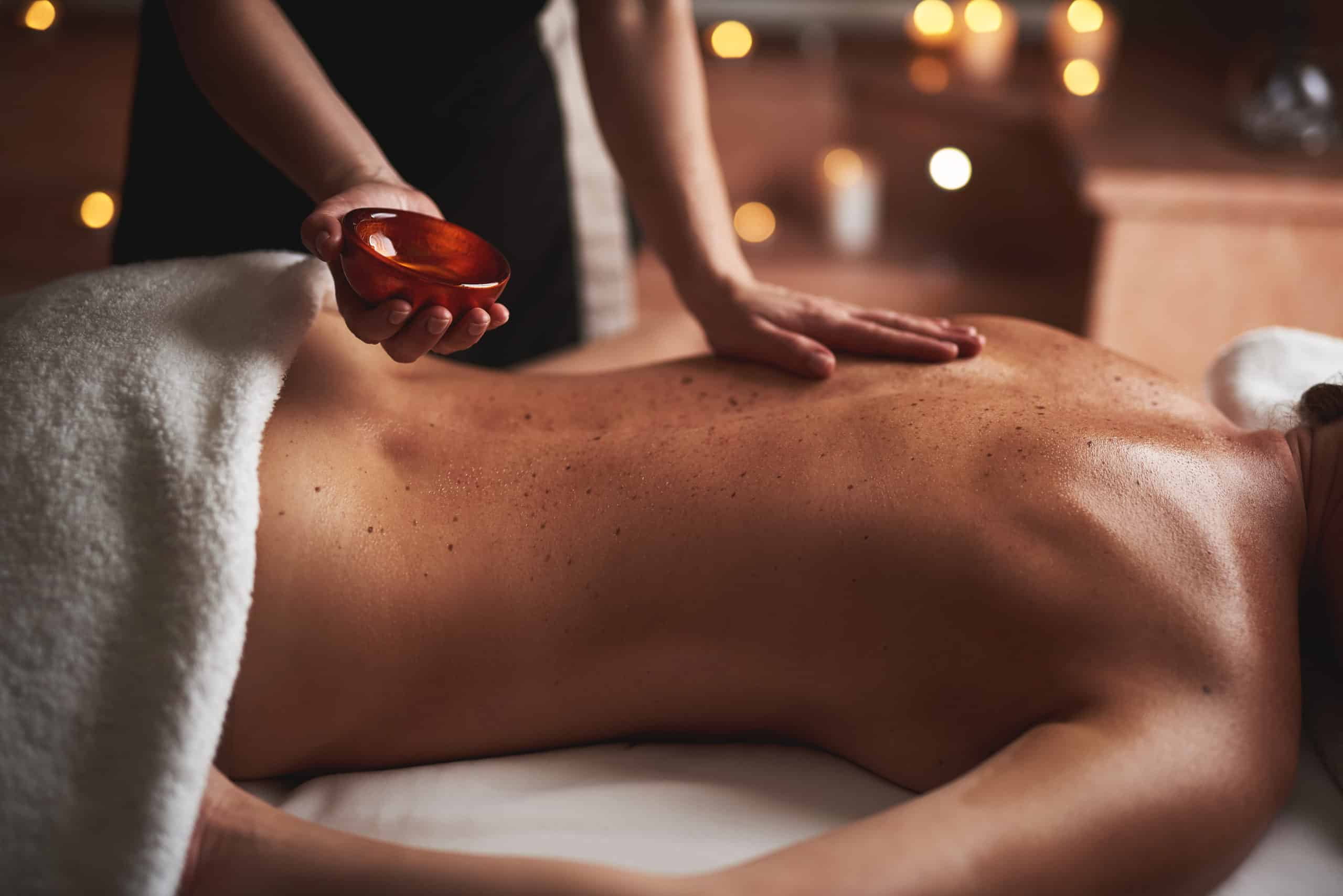 Concept of relaxation and body care. Young lady having relaxing massage in spa salon with essential oils making by female therapist