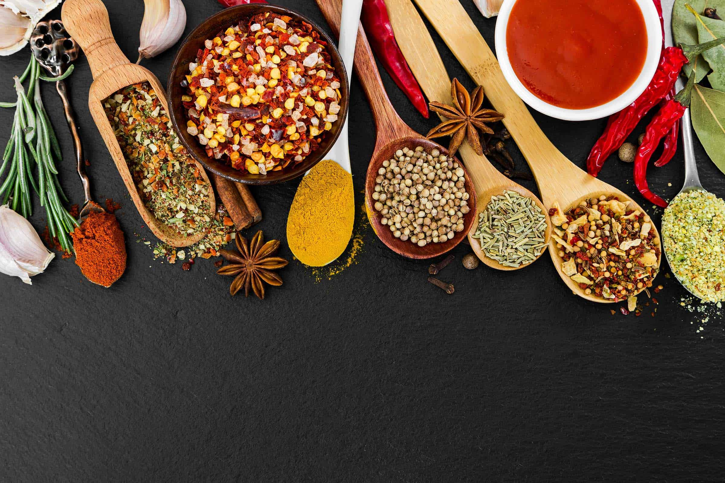 Fragrant seasonings and spices on black background. Top view.